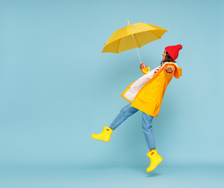 Side view of happy ethnic woman in outerwear and with umbrella leaping and having fun on rainy autumn day on blue background